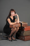 Woman and old suitcases. Young woman and a lot of old suitcases Stock Images