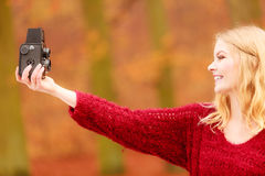 Woman with old vintage camera taking selfie photo. Royalty Free Stock Photos