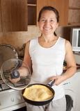 Woman with  omelette in skillet Stock Images