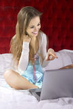 Woman On Bed With Laptop Stock Images