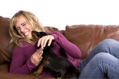Woman On Couch Playing With Dog Royalty Free Stock Photography