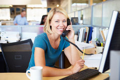 Woman On Phone In Busy Modern Office Royalty Free Stock Photos