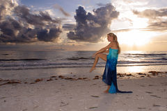 Woman on one leg. A woman is standing on the beach at sunset looking out into the ocean standing on one  leg doing a dance or yoga stretch Stock Images