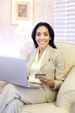Woman Online Shopping. Young attractive Hispanic woman indoors sitting with a laptop and credit card making an on-line purchase Royalty Free Stock Photos