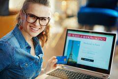 Woman with online travel site on laptop holding blue credit card