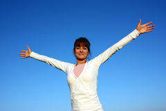 A woman with open arms. Photographed on a blue sky Royalty Free Stock Images