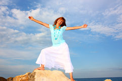 Woman with open arms. Woman with wide open arms step on a rock with cloudy sky and blue sea (ocean) as a background Stock Photos