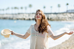 Woman with open arms deep breathing in the beach. Stock Photos