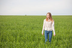 Woman with open arms in the green wheat field at the morning. Woman with open arms in the green wheat field at the morning Royalty Free Stock Photos
