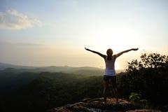 Woman open arms at mountain peak Stock Photos
