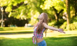Woman with open arms standing outdoors Stock Photography