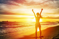Woman open arms at sunset seaside beach Stock Image
