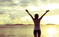 Woman open arms to sunrise Stock Image