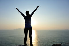 Woman open arms to the sunrise Stock Images