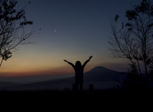 Woman open arms under the sunrise Stock Image