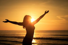 Woman open arms under the sunset at sea. Concept of healthy life Royalty Free Stock Image