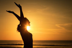 Woman open arms under the sunset at sea. Concept of healthy life Royalty Free Stock Images