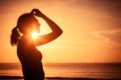 Woman open arms under the sunset at sea. Concept of healthy life Stock Photography