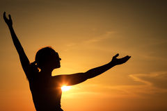 Woman open arms under the sunset at sea. Concept of healthy life Stock Photo