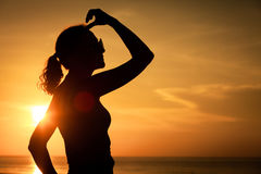Woman open arms under the sunset at sea. Concept of healthy life Royalty Free Stock Photography