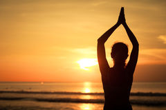 Woman open arms under the sunset at sea. Concept of healthy life Stock Images