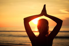 Woman open arms under the sunset at sea. Concept of healthy life Stock Image