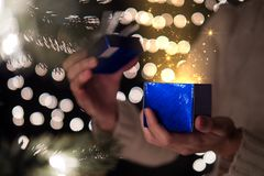 Woman open blue Christmas gift box with golden ray of magic light on bokeh lights background.  Stock Images