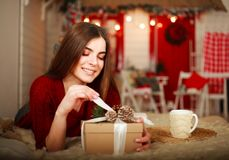Woman open box with gift on background of Christmas decorations Royalty Free Stock Images