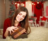 Woman open box with gift on background of Christmas decorations Royalty Free Stock Photography