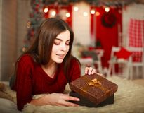 Woman open box with gift on background of Christmas decorations stock images