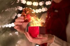 Woman open Christmas gift box with ray of magic light.  Royalty Free Stock Image