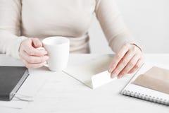 Woman open the envelope. White table Stock Photo