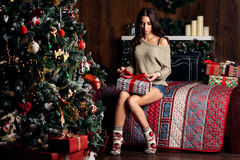 Woman open giftts and christmas tree Stock Images