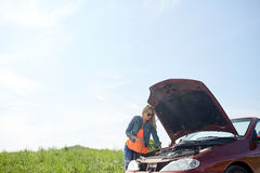 Woman with open hood of broken car at countryside Royalty Free Stock Photos