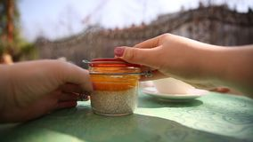 Woman open a jar with chia seeds pudding with mango mousse on the table in cafe. Vegetarian concept. stock footage