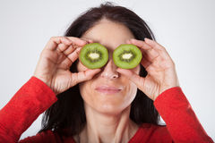 Woman with open kiwis on eye. Face portrait of adult brunette woman with red sweater holding two halves of open kiwi on her eyes royalty free stock photography