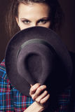 Woman with open lips in black hat on dark background stock image