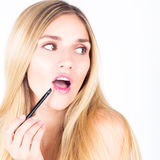 Woman with open mouth applying shine on lips Stock Photo