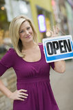 Woman with open sign. Pretty blond woman holding up an open sign with urban background Royalty Free Stock Photo