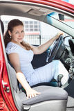Woman through opened door sitting in red car Royalty Free Stock Images
