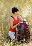 Woman opening backpack. In field Stock Image