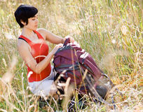 Woman opening backpack in field Stock Image