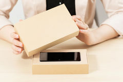 Woman opening box with new smartphone, close-up. Female customer lifting lid from package with her order. Delivery service. online shopping, parcel opening Stock Photography