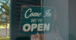 Woman opening cafe or store stock footage