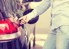 Woman opening car gas tank cap at petrol station Stock Images
