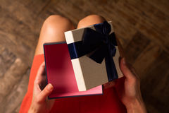 Woman opening a cardboard gift box with blue ribbon Stock Photo