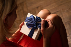Woman opening a cardboard gift box with blue ribbon Stock Photos
