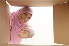 Relocation. Woman opening a carton box and looking inside, relocation and unpacking concept Royalty Free Stock Photos
