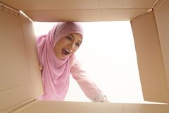 Relocation. Woman opening a carton box and looking inside, relocation and unpacking concept Stock Photography