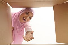 Relocation. Woman opening a carton box and looking inside, relocation and unpacking concept Royalty Free Stock Image
